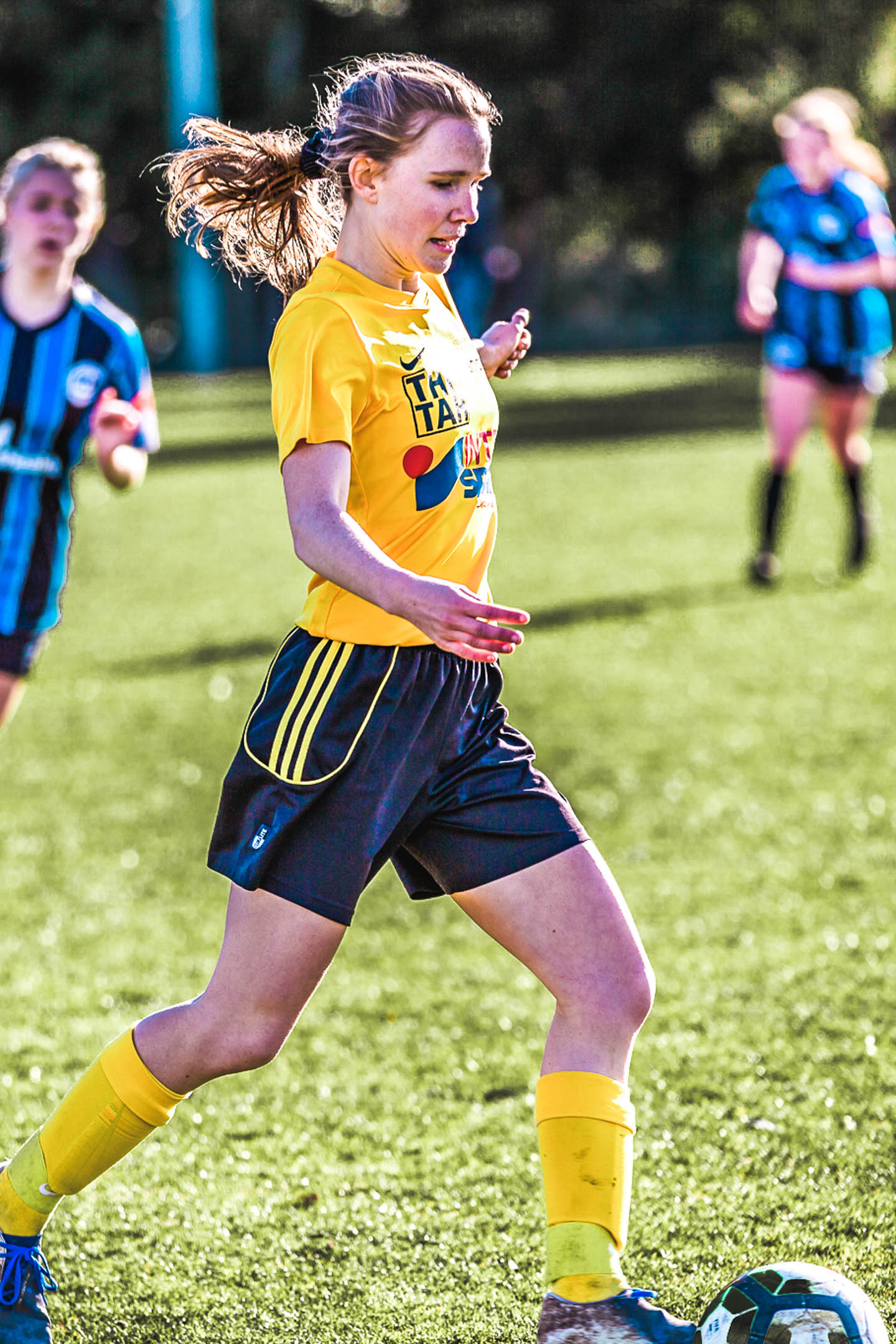 A senior women's player running with the ball